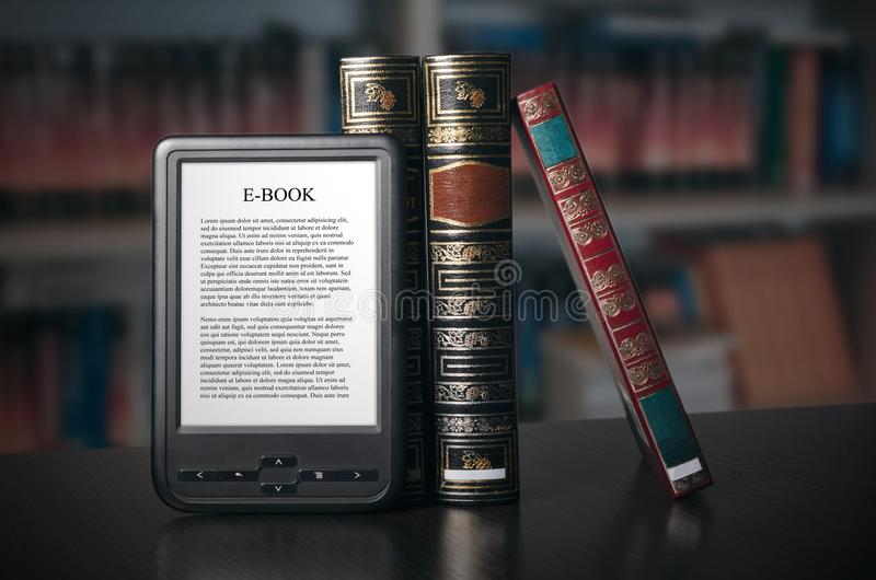 E-book reader device on desk in library. Alternative for traditional books stock images