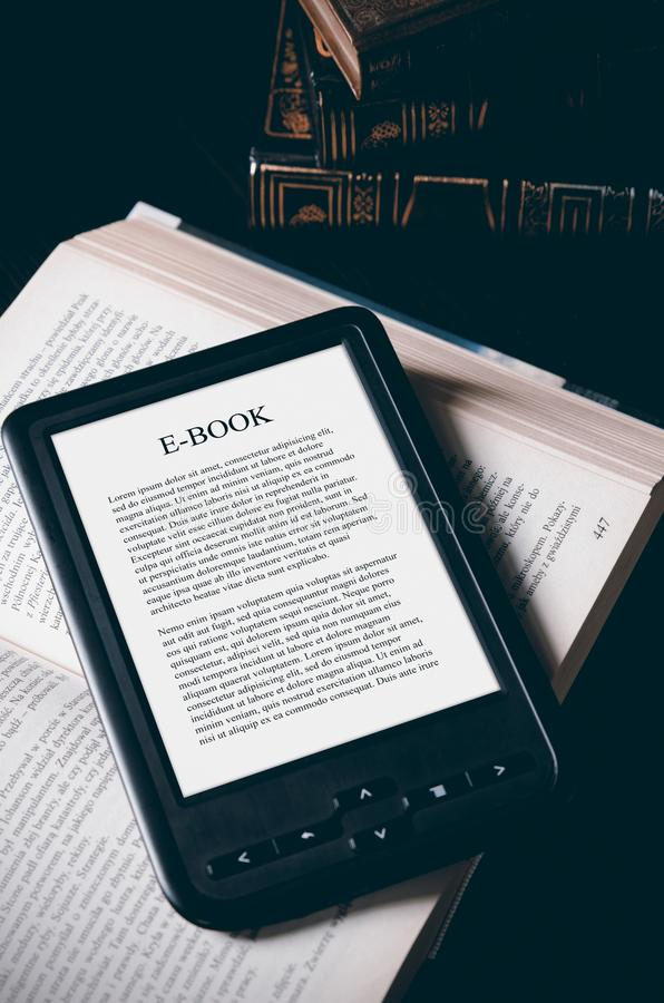 E-book reader device on desk in library. Alternative for traditional books royalty free stock photography