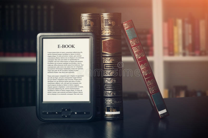 E-book reader device on desk in library. Alternative for traditional books stock photography