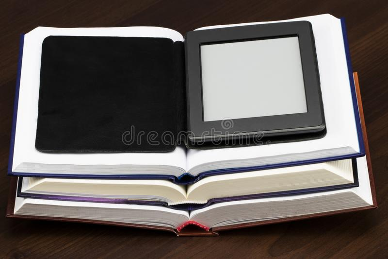 E-book reader device on desk in library. Alternative for traditional books.  stock photo