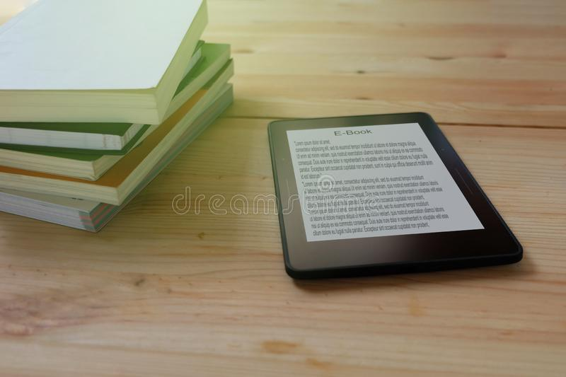 E-book reader and stack of books on wooden stock image