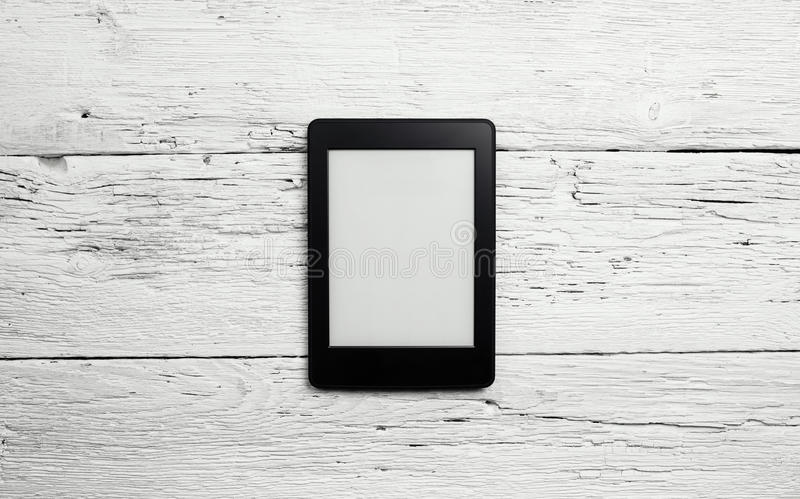 E-book reader or tablet pc on wood. En background royalty free stock photo