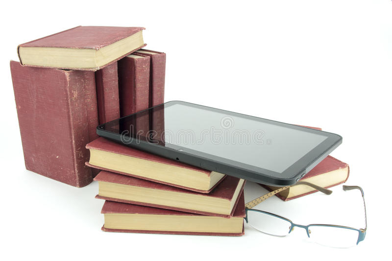 E-book tablet with stack of old printed books and glasses stock photos