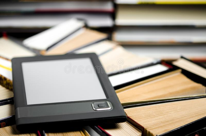 The e-book with a white screen lies on the open multi-colored books that lie on a dark background, close-up. The e-book with a white screen lies on the open stock images