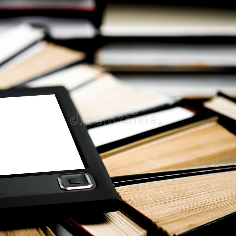 The e-book with a white screen lies on the open multi-colored books that lie on a dark background, close-up. The e-book with a white screen lies on the open royalty free stock photo