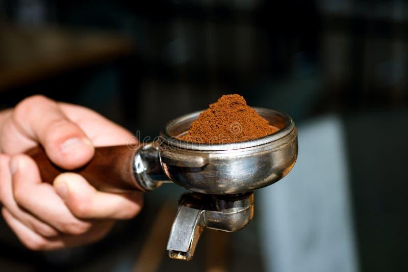 E Cafè moulu frais À café dans le café Portafilter de prise de barman à disposition brassage image libre de droits