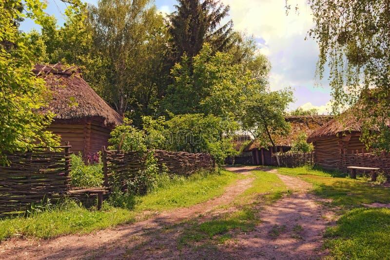 E Camino de tierra típico entre las casas con el jardín en el pueblo ucraniano foto de archivo