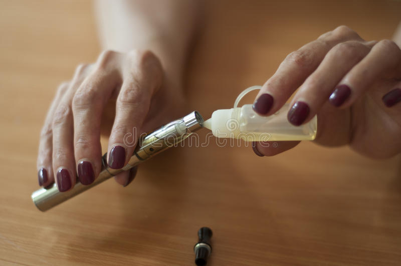 E-cigarette with woman's hands royalty free stock photo