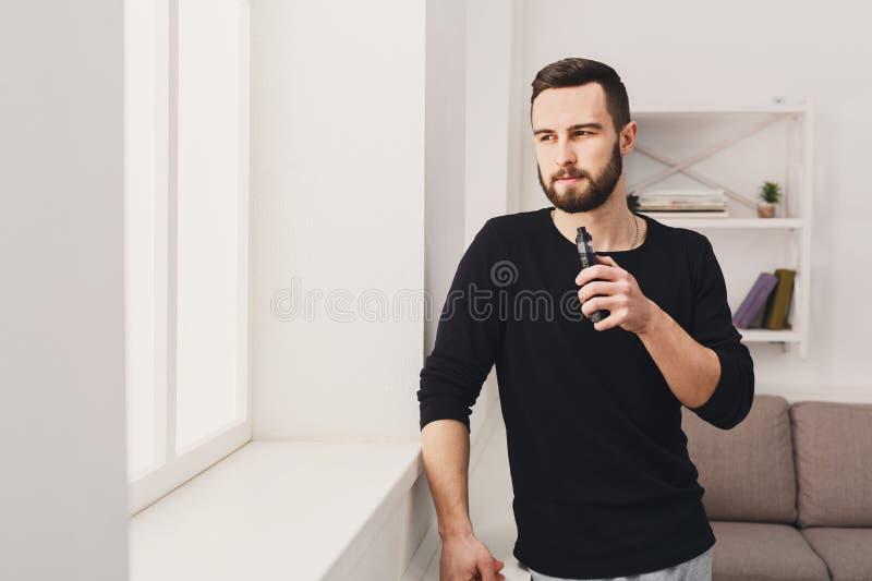 E-cigarrillo vaping del hombre joven en blanco foto de archivo