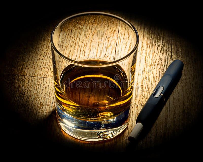 E-cigarrillo y vidrio de alkohole fotografía de archivo
