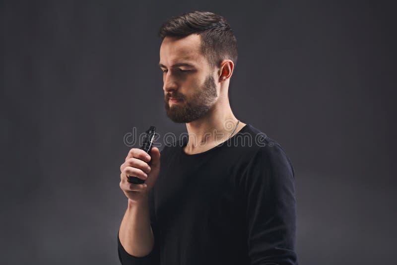 E-cigarro vaping do homem novo no preto imagens de stock royalty free