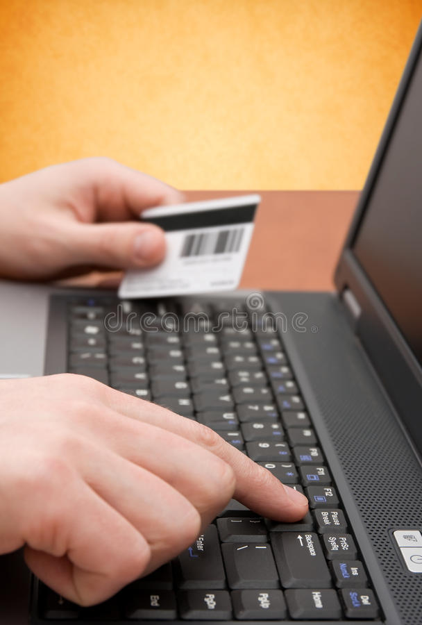 E-commerce concept. Hands with credit card on computer keyboard stock photography