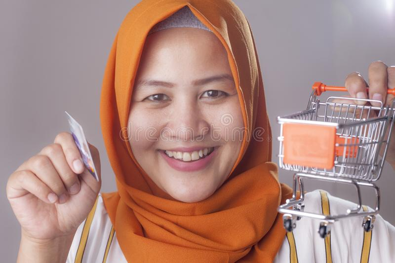 E-commerce Concept, Muslim Lady Holding Mini Trolley and Credit Card. E-commerce concept, Asian muslim lady smiling and holding mini trolley and credit card royalty free stock photography