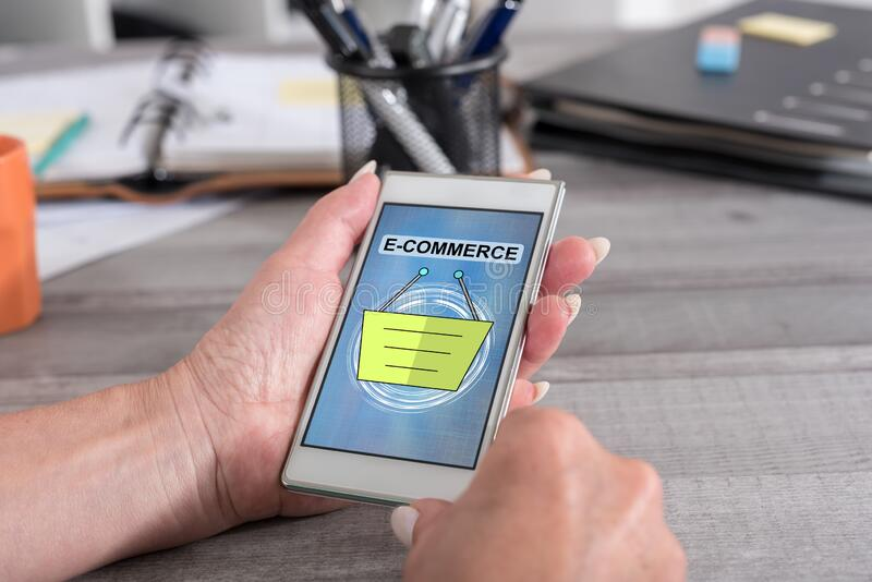 E-commerce concept on a smartphone. Female hand holding a smartphone with e-commerce concept royalty free stock photography