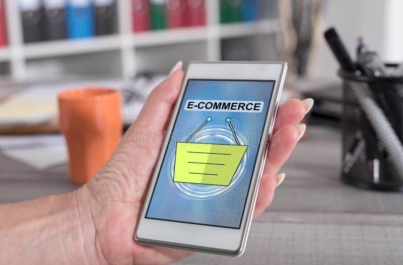 E-commerce concept on a smartphone. Female hand holding a smartphone with e-commerce concept stock photo