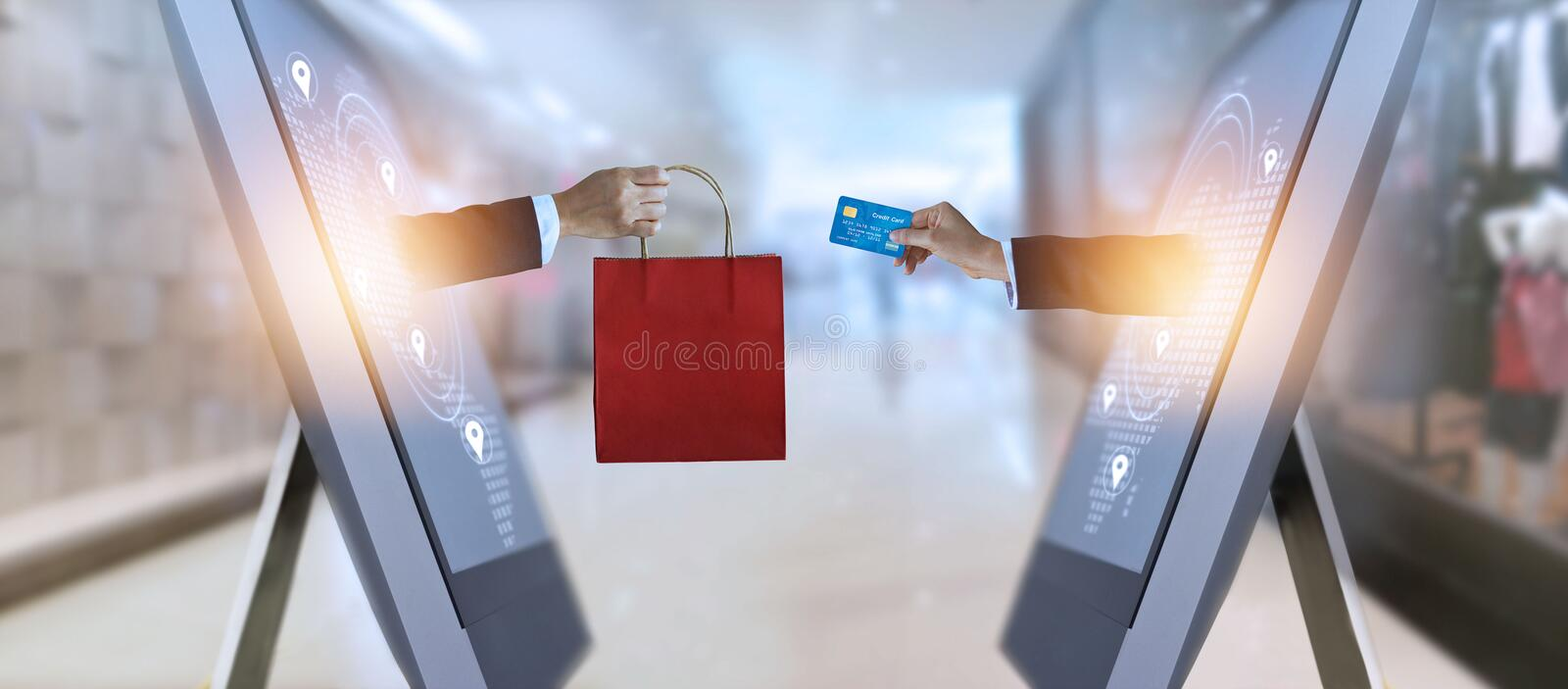E-commerce, hand holding shopping bag and credit card from screen and global network, shopping and payments online concept royalty free stock image