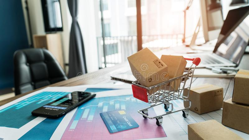 E-commerce. Paper boxes in shopping cart and credit card with smartphone on sales data economic growth graph, online shopping royalty free stock image