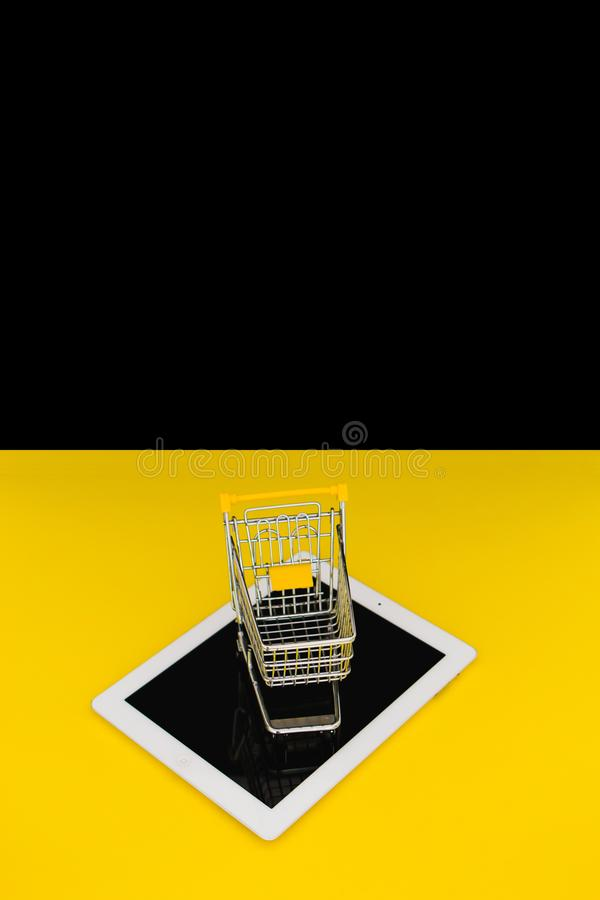 E-commerce and shopping online on internet concept. Small trolley with white digital tablet. Black Friday idea with space for text. E-commerce and shopping stock image