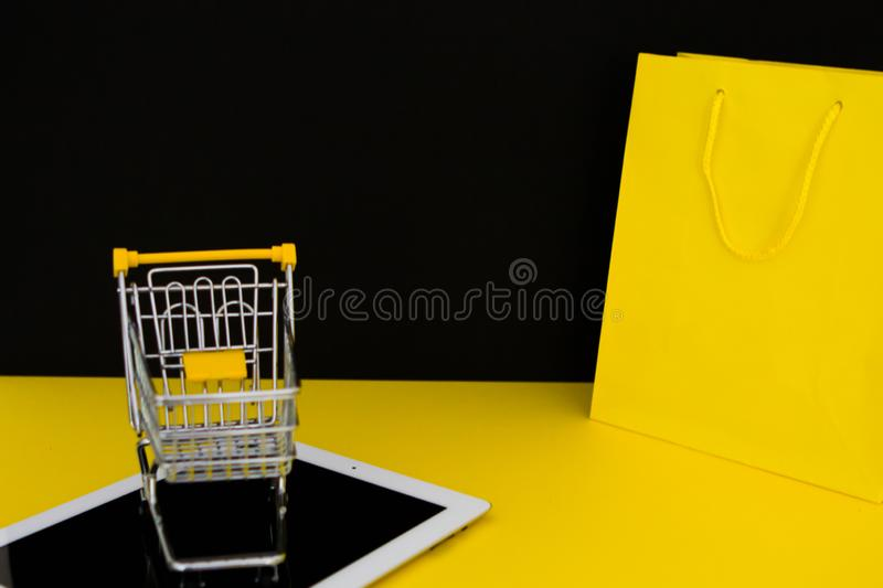 E-commerce and shopping online on internet concept. Small trolley with white digital tablet and yellow shopping bag. Retail and. Black Friday idea with space royalty free stock photography