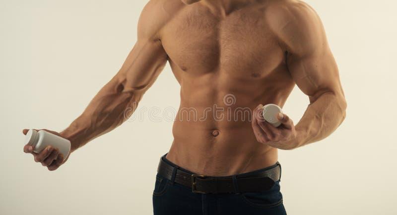 E Crescimento de estimulação do músculo com esteroides anabólicos Garrafas da vitamina da posse do homem forte Homem com seis fotos de stock royalty free