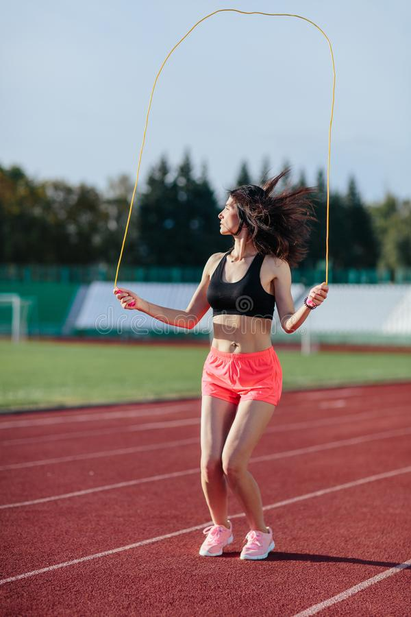 E de vrouw in zwarte bovenkant en nam borrels springend op touwtjespringen op stadion toe Sportief meisje in goede volledige vorm royalty-vrije stock afbeelding