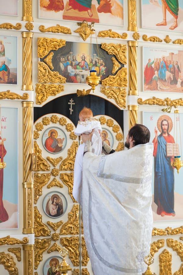 E Den ortodoxa prästen som rymmer, behandla som ett barn under dopritualen royaltyfria foton