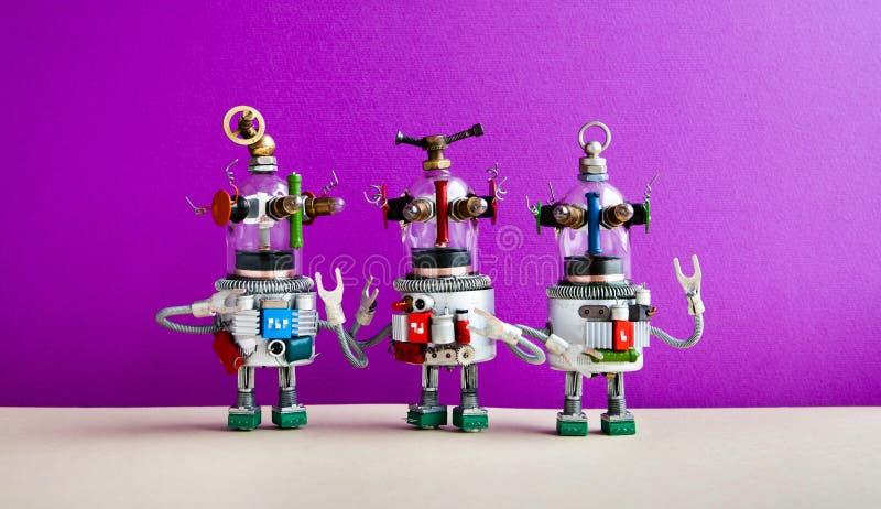 E Drei humanoid Spielzeugroboter stehen in Verbindung stockfoto