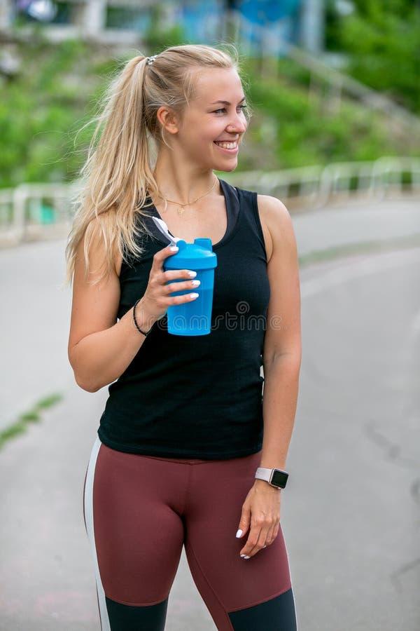 E Drinkt de sporten jonge vrouw water van een fles tijdens een opleiding Training bij het stadion Gezond het levensconcept royalty-vrije stock afbeelding