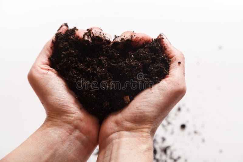 E Due mani che tengono una manciata di suolo a terra r immagini stock