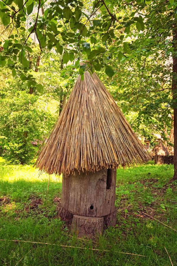 E Een oude bijenbijenkorf Het maakte van een boomstam van oude boom met een met stro bedekt dak stock afbeeldingen