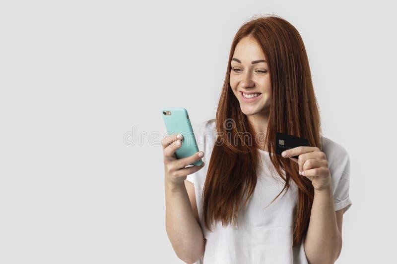 E Ella sostiene el teléfono y la tarjeta de crédito en su mano El concepto imágenes de archivo libres de regalías