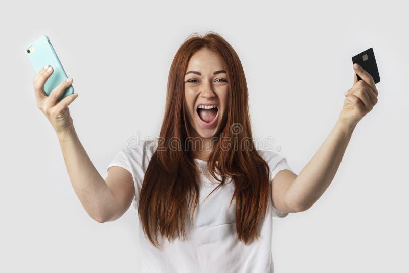 E Ella sostiene el teléfono y la tarjeta de crédito en su mano El concepto imagenes de archivo