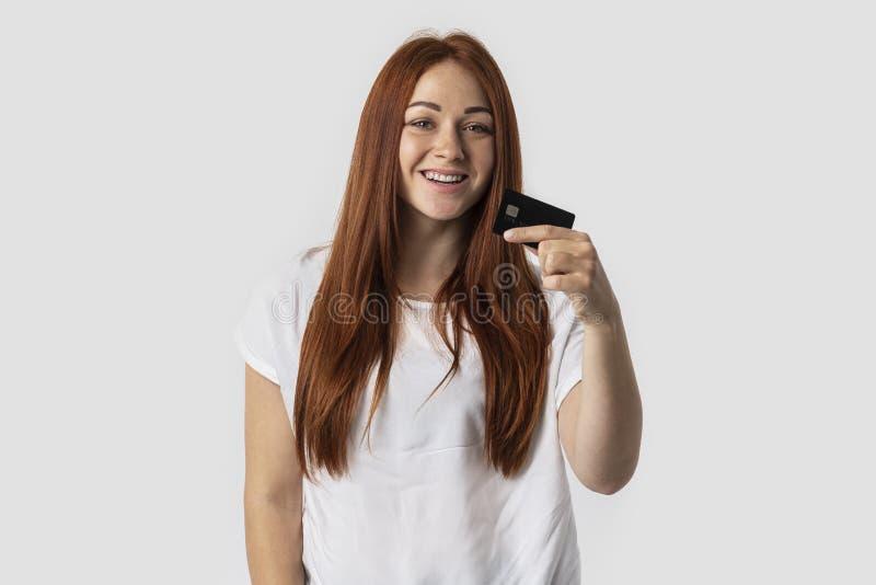 E Ella sostiene una tarjeta de crédito en su mano El concepto de compras foto de archivo