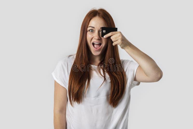 E Ella sostiene una tarjeta de crédito en su mano El concepto de compras foto de archivo libre de regalías
