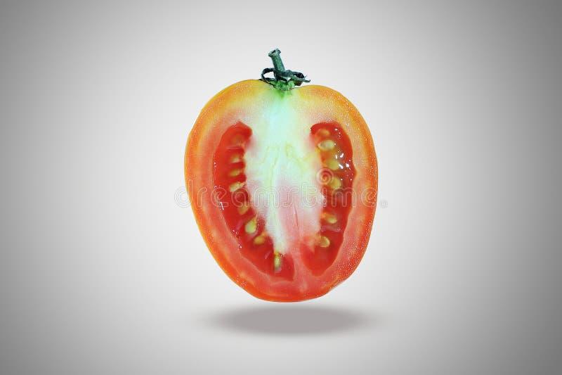 E en halva av tomaten, skivatomat, flyger tomaten som isoleras på mörk karaktärsteckning royaltyfri fotografi