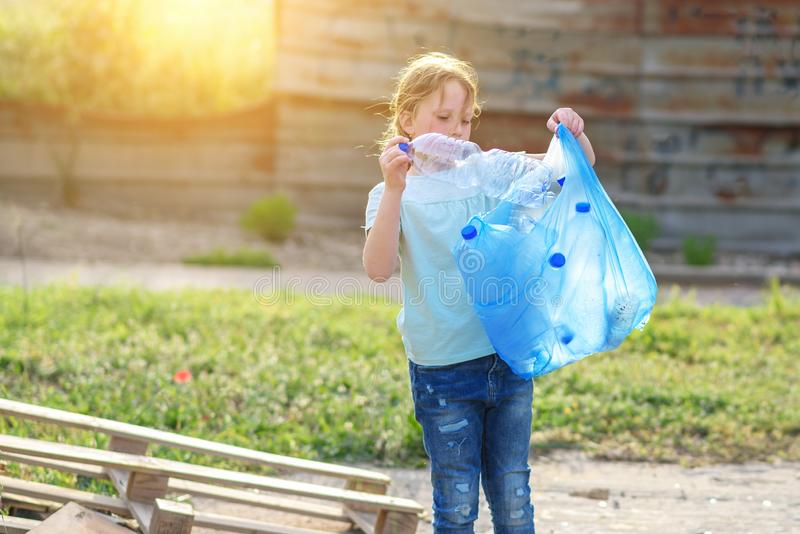 E Enfant volontaire avec un sac de d?chets nettoyant des ordures, mettant la bouteille en plastique en r?utilisant le sac photographie stock