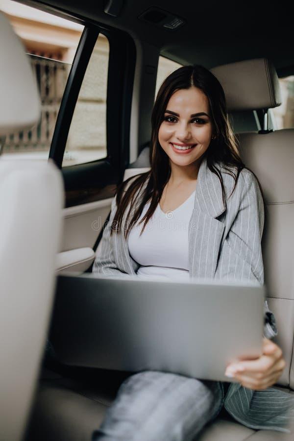 E Entrepreneur féminin travaillant pendant le déplacement au bureau dans une voiture de luxe photographie stock