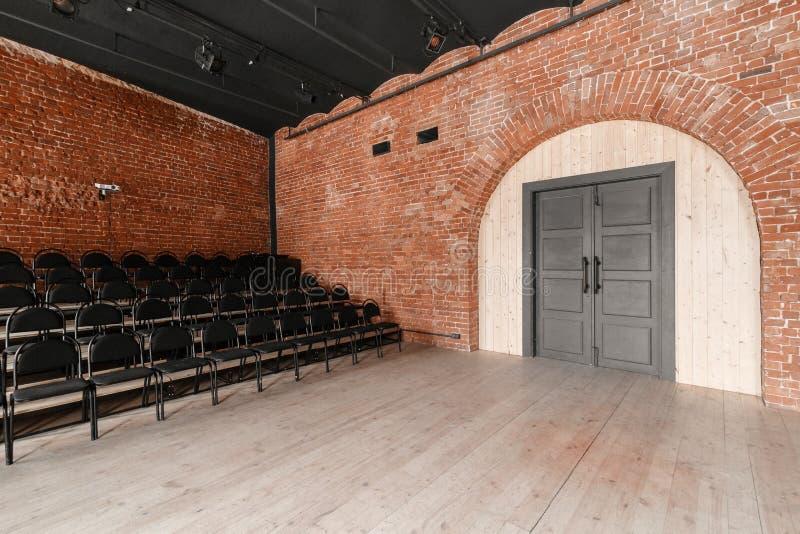 E Estilo do sótão Salão com as cadeiras pretas para webinars e conferências Uma sala enorme com grande Windows, cercado foto de stock