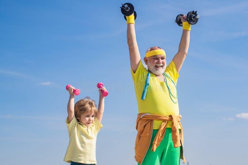 E Eu amo o esporte o Avô do desportista e criança saudável com peso fotografia de stock