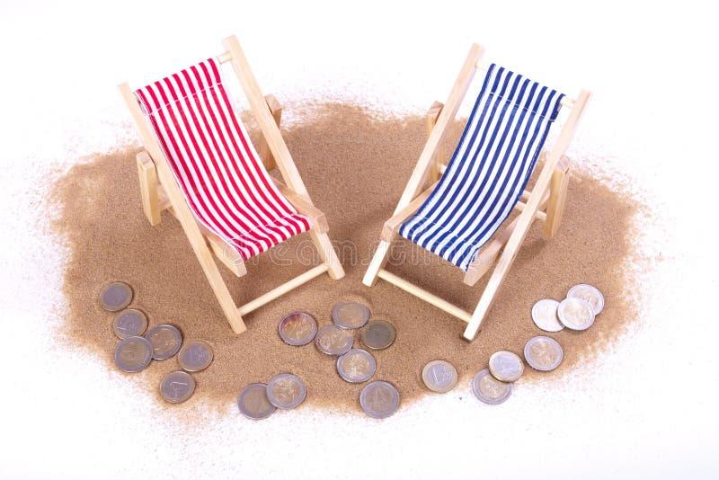 1 e 2 euro- moedas encontram-se na frente das cadeiras de praia do brinquedo fotos de stock