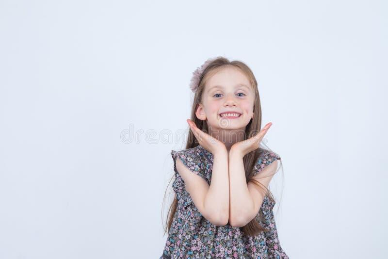 E Expressions drôles et heureuses Avoir l'amusement Élève du cours préparatoire dans la robe sur le fond blanc photo stock