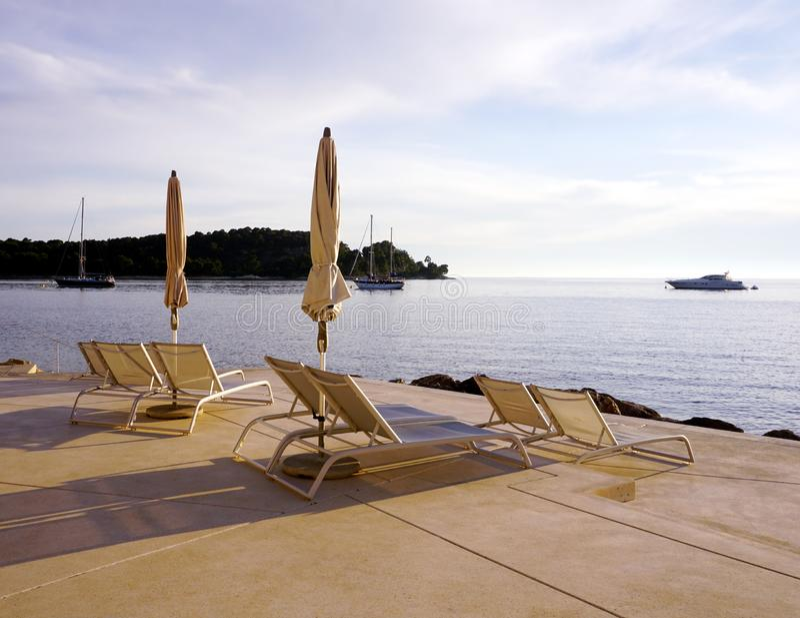 E Férias e conceito de relaxamento com cadeiras do sol e guarda-chuva de sol no recurso pelo mar imagens de stock