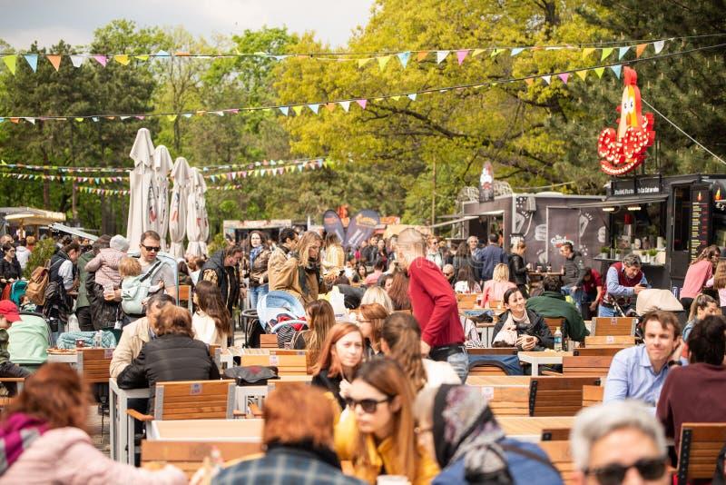E 04 2019 - Festival del camión de la comida de la calle - gente que se sienta y que come en sus tablas en una comida imagen de archivo