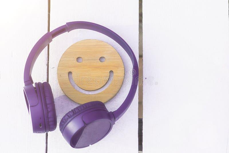E Fones de ouvido roxos sem fio e um sorriso de madeira em um fundo branco Tecnologias novas fotos de stock
