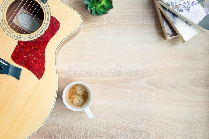 E Gitarr, böcker, kopp kaffe och suckulenta växter över träbakgrund kopiera avst?nd arkivbilder