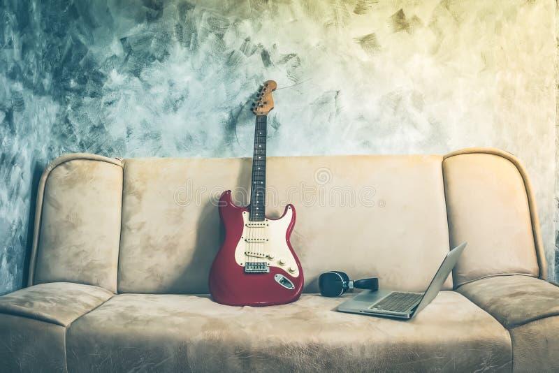 E-Gitarre mit Laptop und Kopfhörer auf einem Sofa Weinlesetonne lizenzfreies stockbild