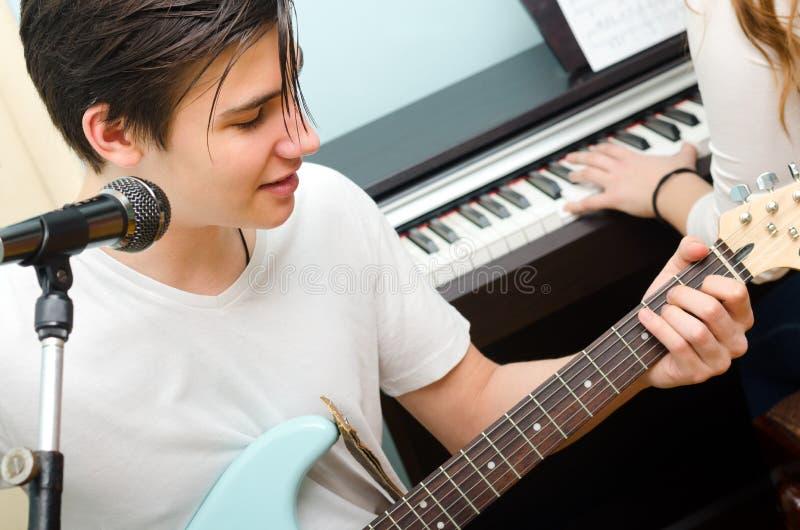 E-Gitarre spielender und singender Teenager während Mädchenspiele stockfoto
