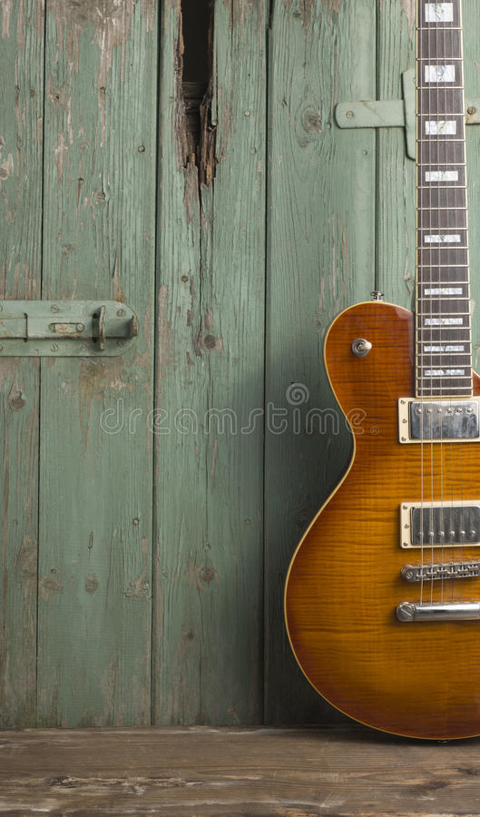 E-Gitarre vor grünem Weinlesehintergrund lizenzfreie stockbilder