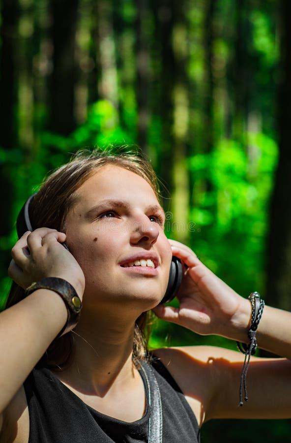 E Glückliche junge Frau, die Musik mit Kopfhörern im Wald hört stockfotos