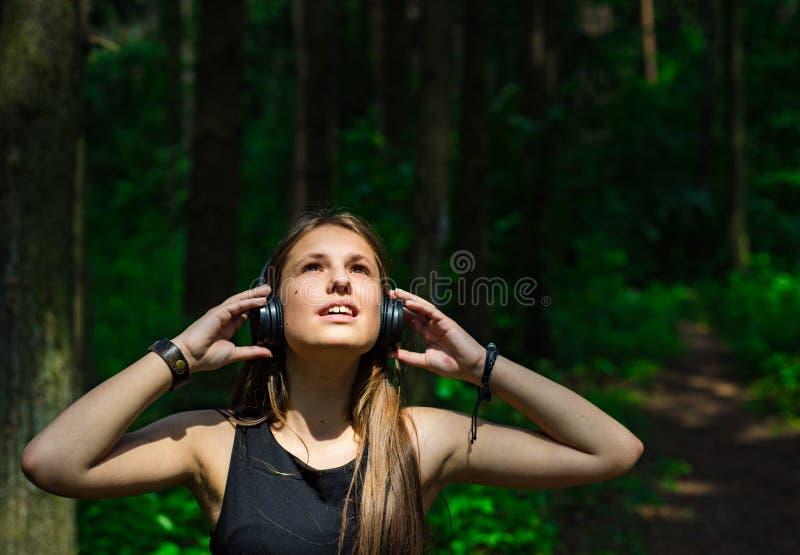 E Glückliche junge Frau, die Musik mit Kopfhörern im Wald hört lizenzfreies stockfoto